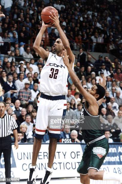 View of American college basketball player Richard 'Rip' Hamilton of the University of Connecticut as he jumps with the ball during a game against...