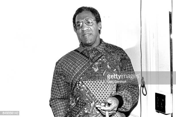 View of American comedian and actor Bill Cosby as he smokes a cigar backstage at Radio City Music Hall, New York, New York, January 31, 1986.