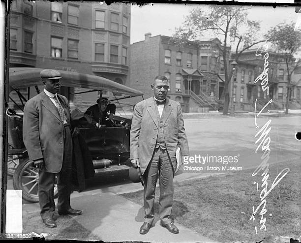 Booker T Washington standing on a sidewalk by an automobile Chicago Illinois 1911