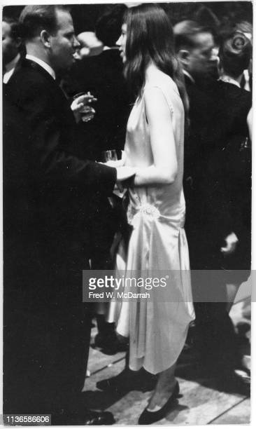 View of American feminist activist author and critic Jill Johnston as she speaks with an unidentified man during a party at the Museum of Modern Art...
