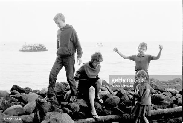 View of American feminist author and social activist Betty Friedan on a rocky beach with her children, from left, Daniel, Jonathan , and Emily, New...