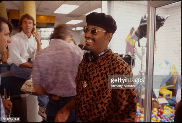 View of American film director John Singleton in sunglasses and a beret as he smiles on the set of his movie 'Poetic Justice' Los Angeles California...