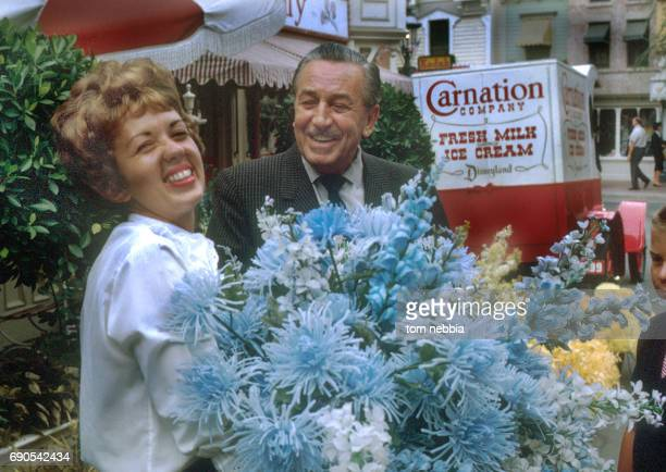 View of American film producer and studio executive Walt Disney shares a laugh with an unidentified woman at the Main Street Flower Mart of...