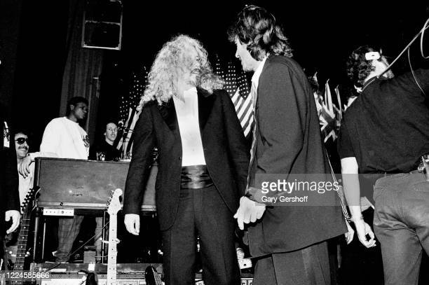 View of American Folk musician Arlo Guthrie and British Rock and Pop musician George Harrison as they talk together onstage during the Third Annual...