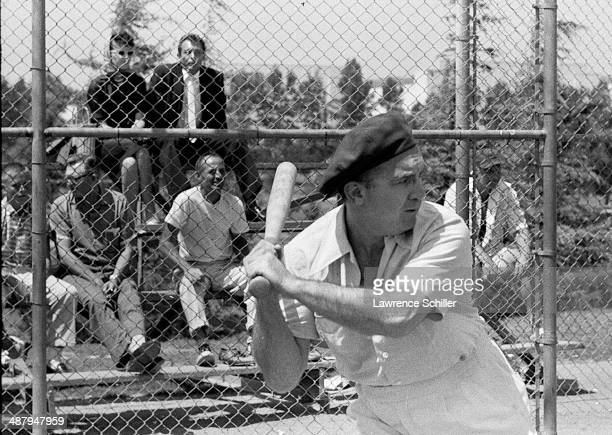 View of American gangster Mickey Cohen at bat during a softball game on a lot across from the Twentieth Century Fox Studios Los Angeles California...