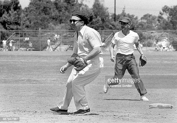 View of American gangster Mickey Cohen plays second base during a softball game on a lot across from the Twentieth Century Fox Studios Los Angeles...