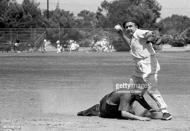 View of American gangster Mickey Cohen prepares to throw the ball from second base during a softball game on a lot across from the Twentieth Century...