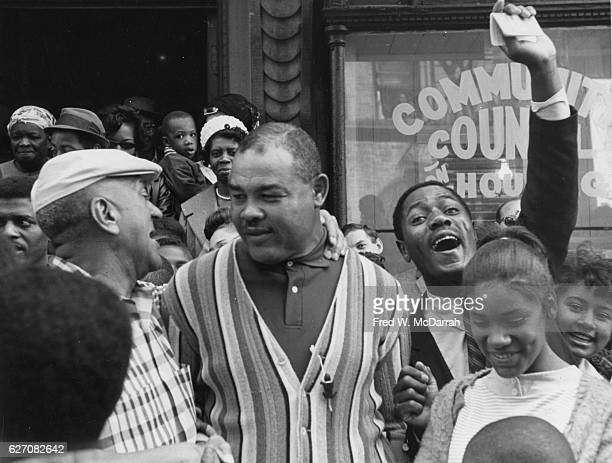 View of American heavyweight boxer Joe Louis as he talks with people on an unspecified Harlem street New York New York May 30 1964