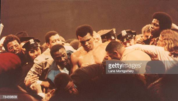 View of American heavyweight boxer Muhammad Ali surrounded by associates fans and police officers after a bout at Madison Square Garden New York New...
