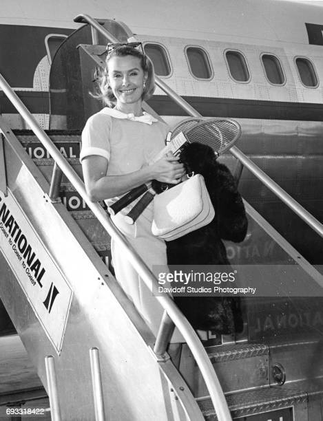 View of American heiress and businesswoman Dina Merrill a fur coat and a pair of tennis racquets in her hands as she deplanes from a National...