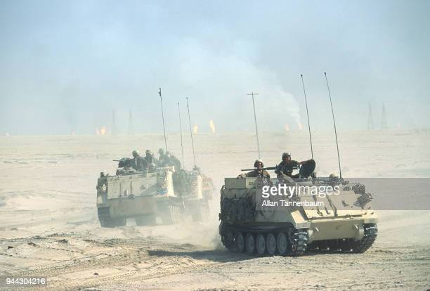 View of American M113 Armored Personnel Carriers as they cross the desert during the Gulf War Iraq Burning oil wells are visible in the background
