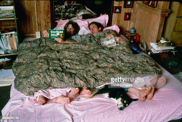 View of American married couple actress Jane Fonda and politician and activist Tom Hayden in bed as the former reads aloud from 'Garfield Bigger Than...