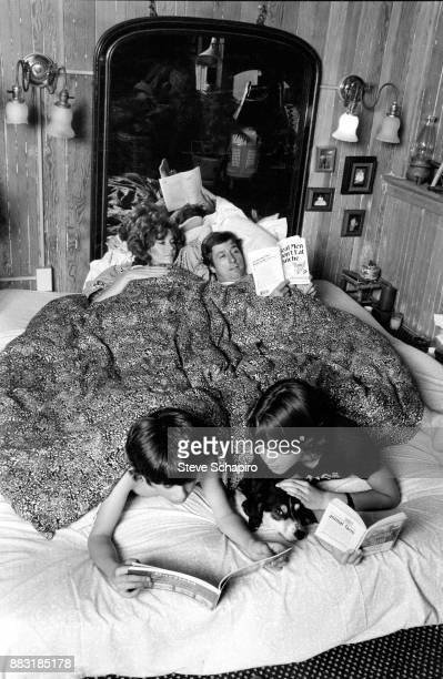 View of American married couple actress Jane Fonda and politician and activist Tom Hayden in bed as the latter reads Bruce Feirstein's 'Real Men...