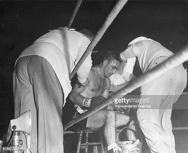 View of American middleweight boxer Carmen Basilio as he sits between his cornermen during a bout New York New York September 1959