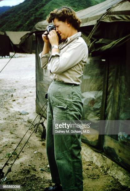 View of American military anesthetist Millie Rush of the 8063rd MASH as she takes photographs outside a US Army tent South Korea January 1952