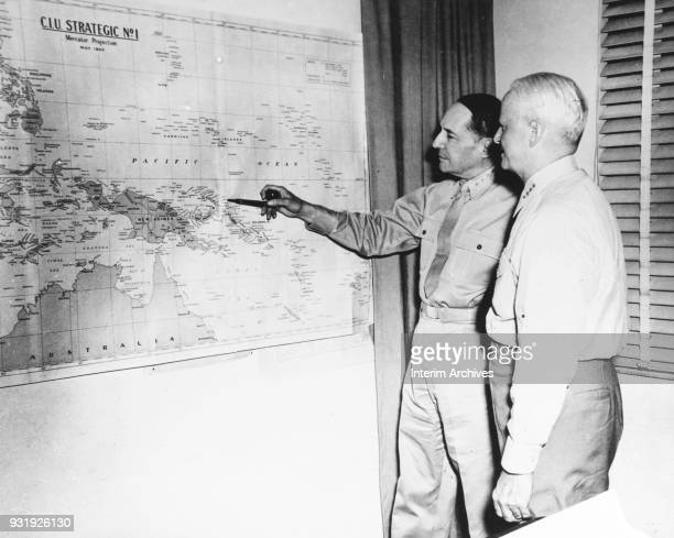 View of American military commanders General Douglas MacArthur and Admiral Chester Nimitz look at a map of the Pacific Ocean as they discuss strategy...