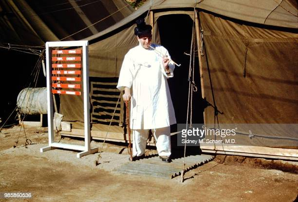 View of American military surgeon Captain Sidney Schaer of the 8063rd MASH dressed in traditional Korean clothing as he smokes a long pipe outside a...