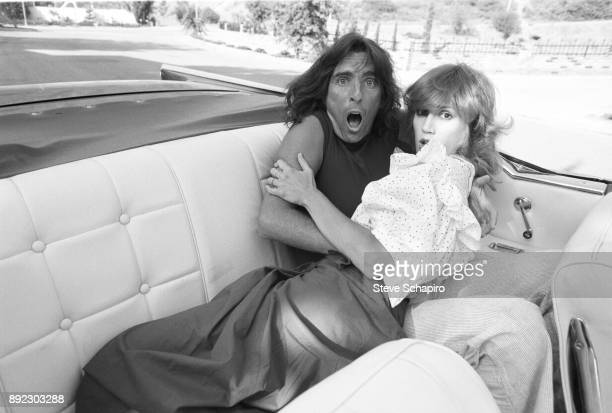 View of American musician Alice Cooper and his wife choreographer Sheryl Cooper as they mime surprise from the back seat of a convertible Los Angeles...