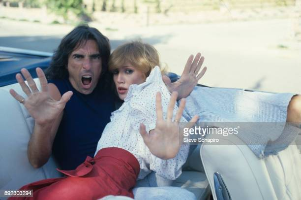 View of American musician Alice Cooper and his wife choreographer Sheryl Cooper as they hold out their palms from the back seat of a convertible Los...