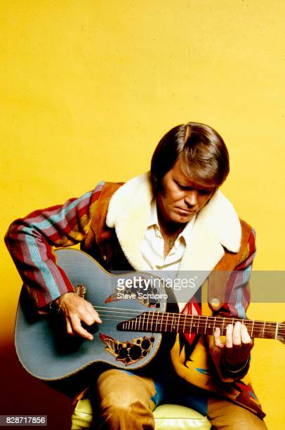 View of American musician Glen Campbell as he plays guitar in front of a yellow backdrop Los Angeles California 1978