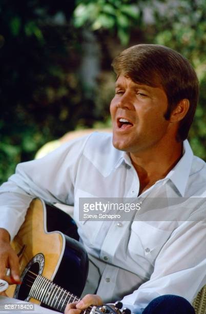 View of American musician Glen Campbell as he plays guitar outdoors Los Angeles California 1978