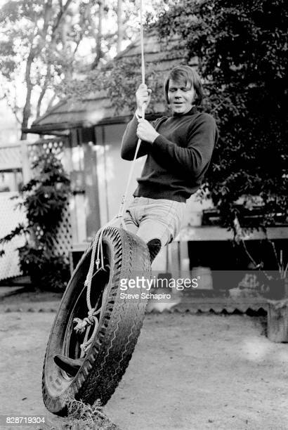 View of American musician Glen Campbell on a tire swing outside his home Los Angeles California 1978