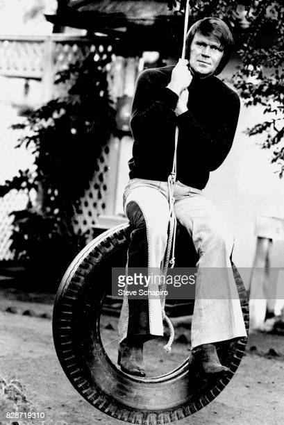 View of American musician Glen Campbell on a tire swing outside his home, Los Angeles, California, 1978.