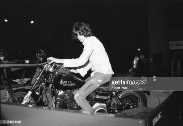 View of American musician Joey Ramone as he sits on a Harley Davidson motorcycle which in turn sits in a back of a GMC pickup truck New York New York...