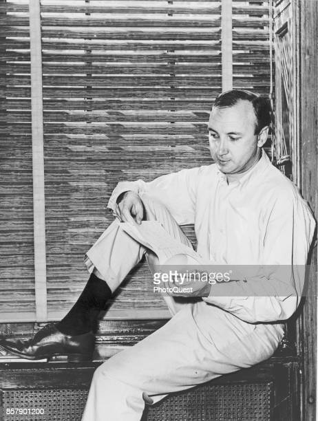 View of American playwright and author Neil Simon as he sits on a windowsill in his home New York New York 1966