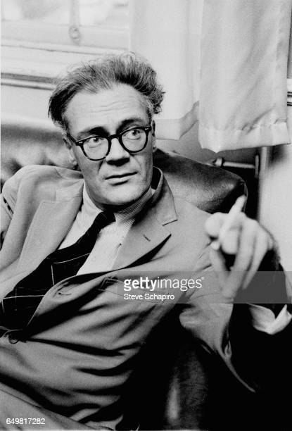 View of American poet Robert Lowell a cigarette in his band as he sits on a sofa Boston Massachusetts 1964