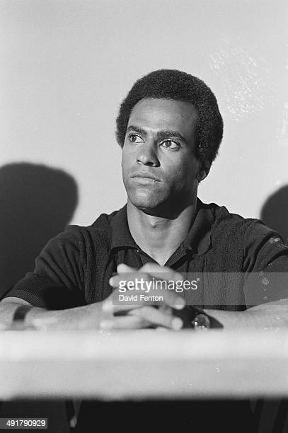 View of American political and social activist Black Panther Minister of Defense Huey Newton as he sits at a table during an unspecified event circa...
