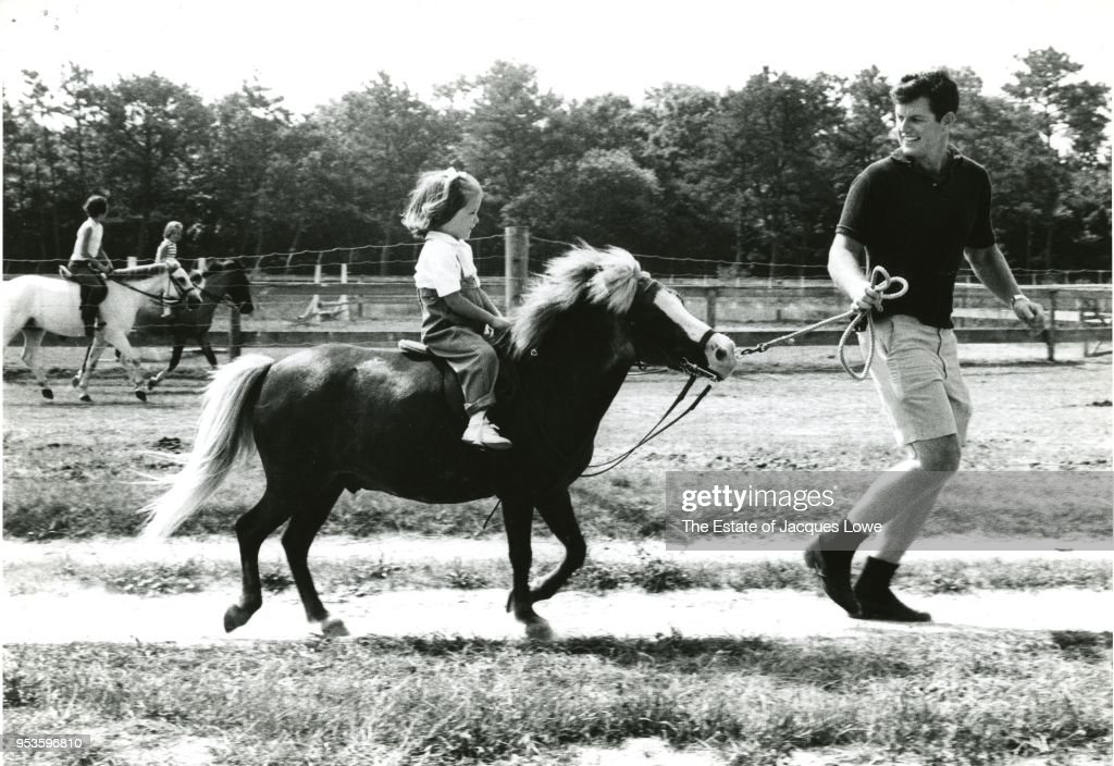 View of American politician US Senator Ted Kennedy (1932 - 2009) as he leads his daughter, Kara (1960 - 2011), on a pony, mid 1960s