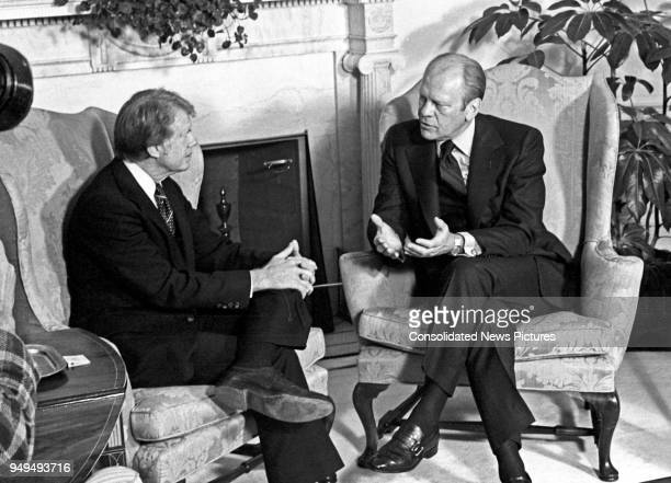 View of American politicians US President-Elect Jimmy Carter and US President Gerald Ford as they talk together in the White House's Oval Office,...