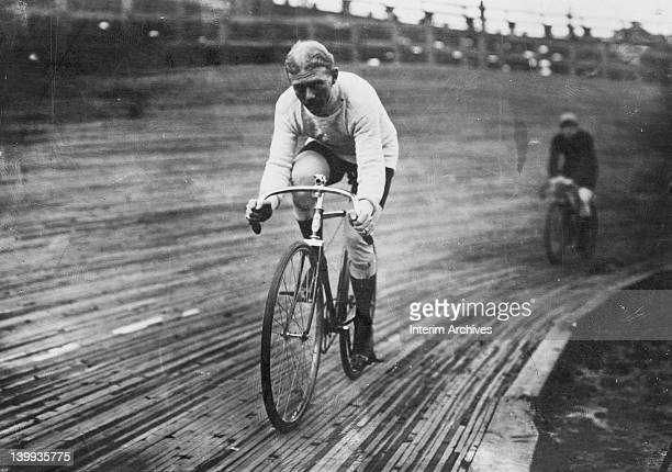 View of American professional cyclist Robert Walthour pictured on his bicycle riding on a wooden tracked velodrome during a six day race December 1909
