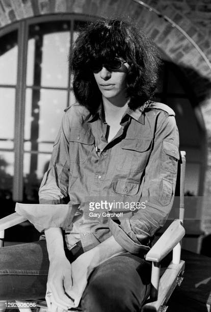 View of American Punk Rock musician Joey Ramone as he sits in a director's chair during an interview at MTV Studios, New York, New York, April 1,...