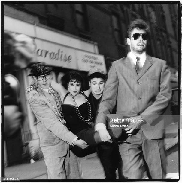 View of American Rap group the Beastie Boys as they carry an unidentified woman in an evening gown along a street in Times Square New York New York...