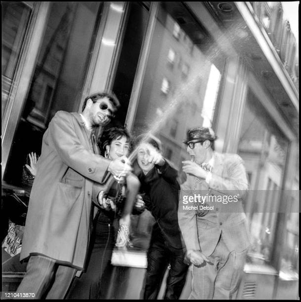 View of American Rap group the Beastie Boys with Eloise, their stage dancer, with a bottle of champagne, along a street in Times Square, New York,...