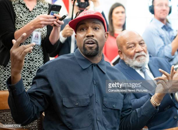 View of American rapper and producer Kanye West gesturing with his hands in the White House's Oval Office Washington DC October 11 2018 He wears a...