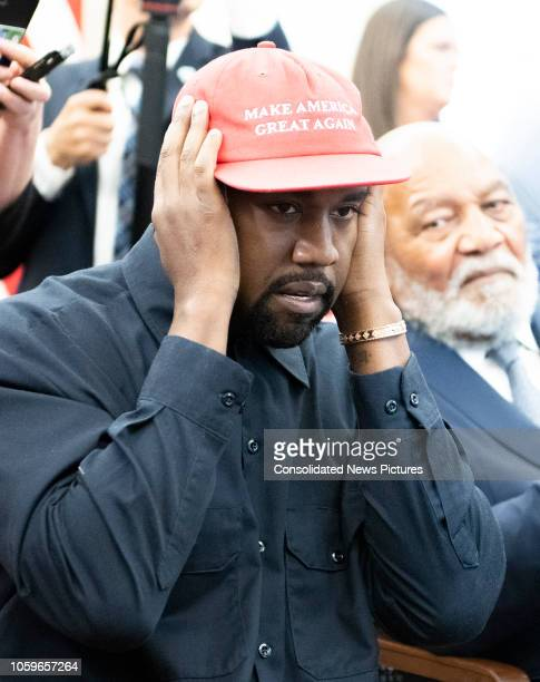 View of American rapper and producer Kanye West, his hands over his ears, in the White House's Oval Office, Washington DC, October 11, 2018. He wears...