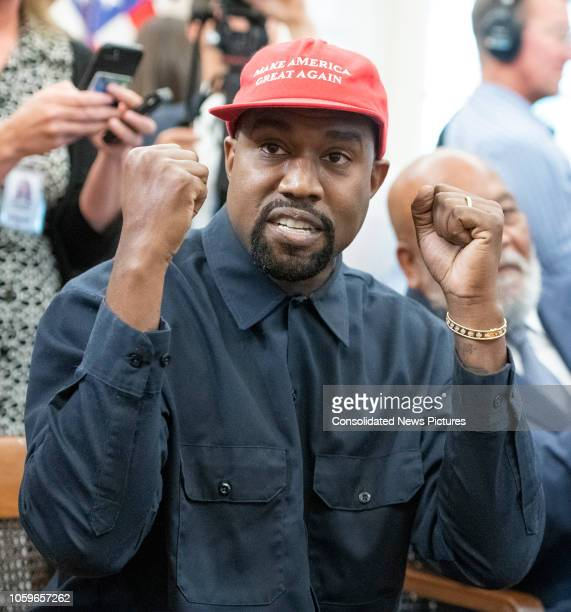 View of American rapper and producer Kanye West with his fists raised in the White House's Oval Office Washington DC October 11 2018 He wears a red...