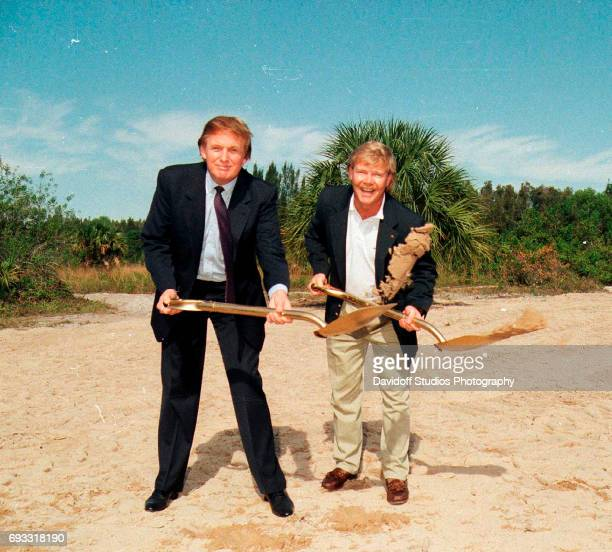 View of American real estate developer Donald Trump and an unidentified man each with a 'golden' shovel at the Trump International Golf Club...