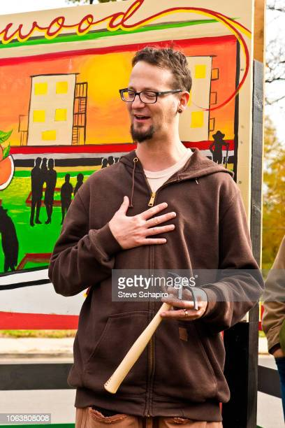 View of American religious activist and author Shane Claiborne as he holds a hand rake during a demonstration at an antigun rally in the Englewood...