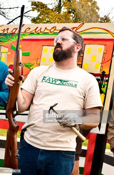View of American religious activist and blacksmith Michael Martin of the RAWTools organization as he holds a rifle in hand and a garden tool in the...