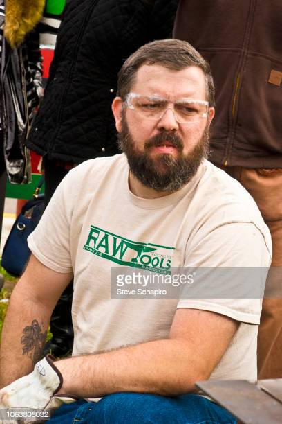 View of American religious activist and blacksmith Michael Martin of the RAWTools organization as he kneels down during a demonstration at an antigun...