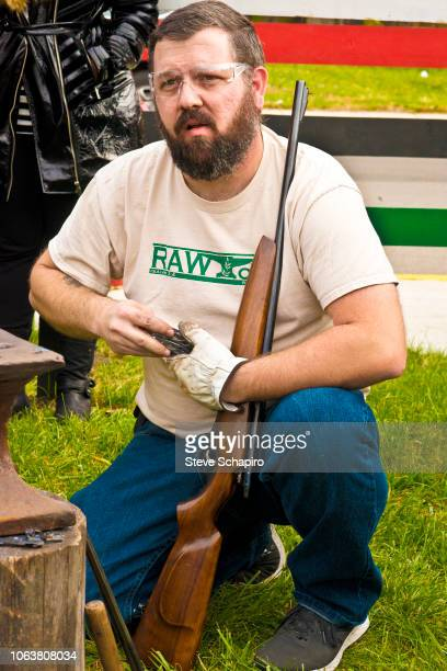 View of American religious activist and blacksmith Michael Martin of the RAWTools organization as he kneels down with a rifle during a demonstration...