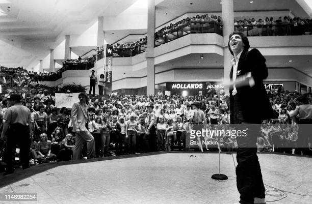 View of American Rock musician Rick Springfield as he stands onstage during a promotional appearance at the Woodfield Mall, Schaumberg, Illinois,...