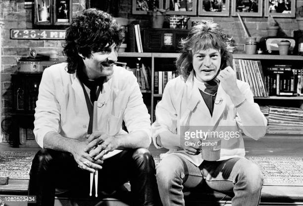 View of American Rock musicians Carmine Appice , who holds a pair of drumsticks, and Rick Derringer, who holds an MTV mug, both of the group DNA, as...