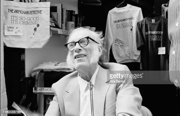 View of American science fiction mystery writer Isaac Asimov as he sits in a booth during the 'New York is Book County' fair New York New York...