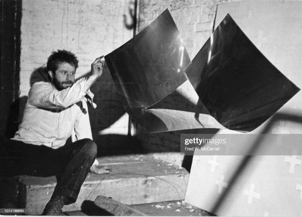 View of American sculptor Mark di Suvero as poses with his work in his loft studio (on Fulton Street), New York, New York, November 20, 1965.