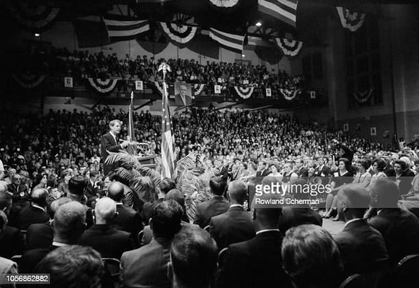 View of American senator Robert F Kennedy on a podium surrounded by supporters as he speaks into microphones at an unspecifed rally during his...